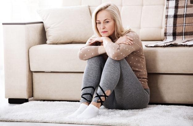 Woman on the floor wondering is addiction a choice