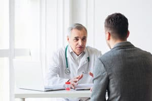 a doctor talking to a patient about PTSD treatment program