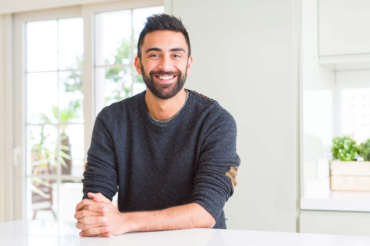 A man sits at a kitchen table and smiles, enjoying recovery from addiction