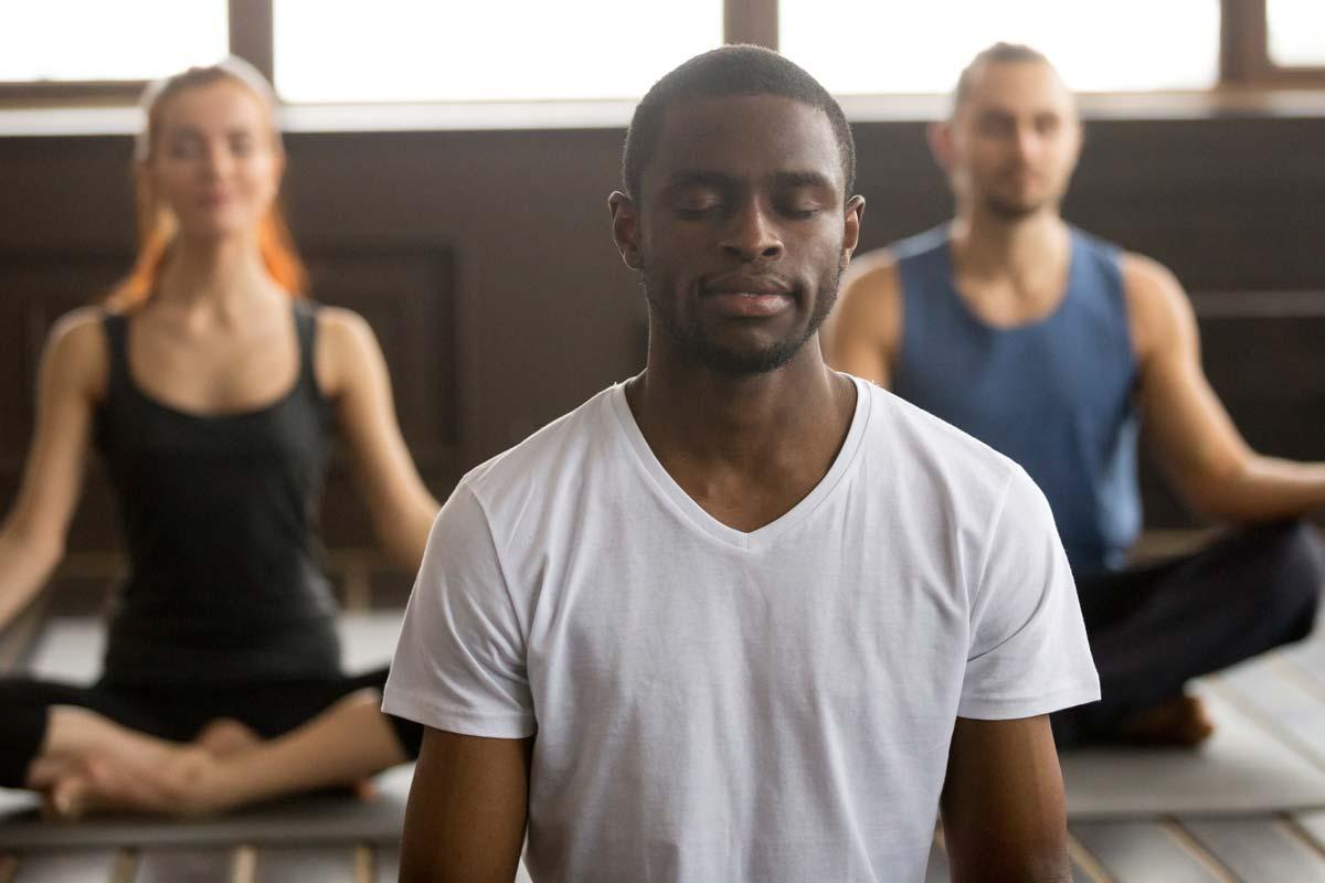 A man practices yoga as part of his stress management techniques