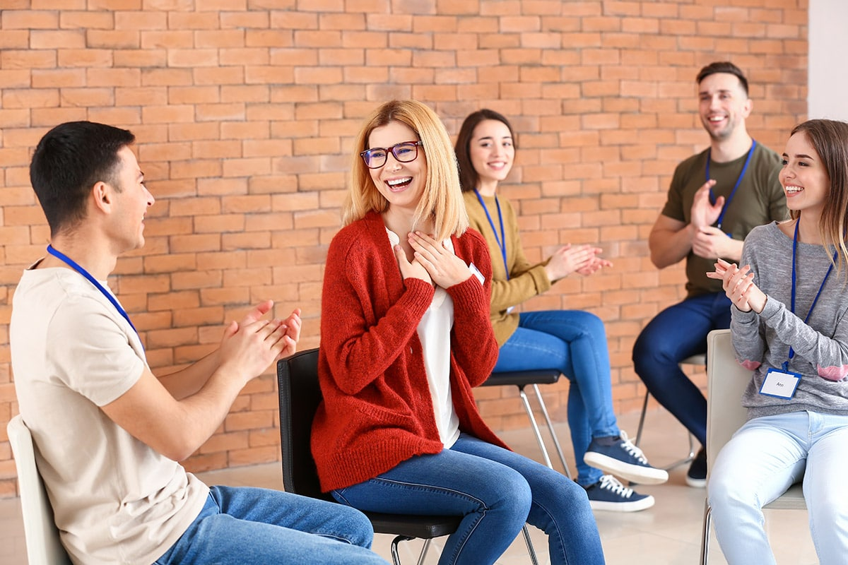 a group applauding someone making a breakthrough as a benefits of group therapy