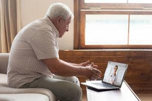 older man using laptop for telehealth intensive outpatient program