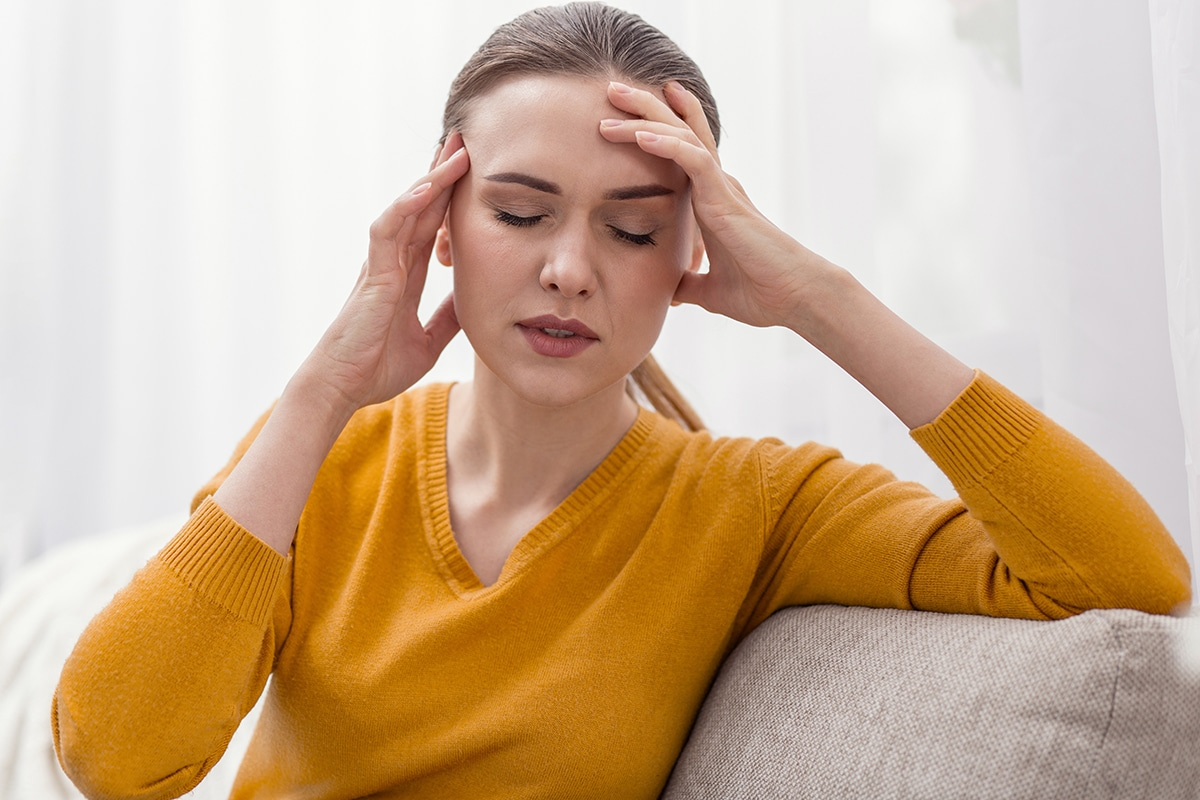woman holding head because she senses signs of an anxiety attack coming on