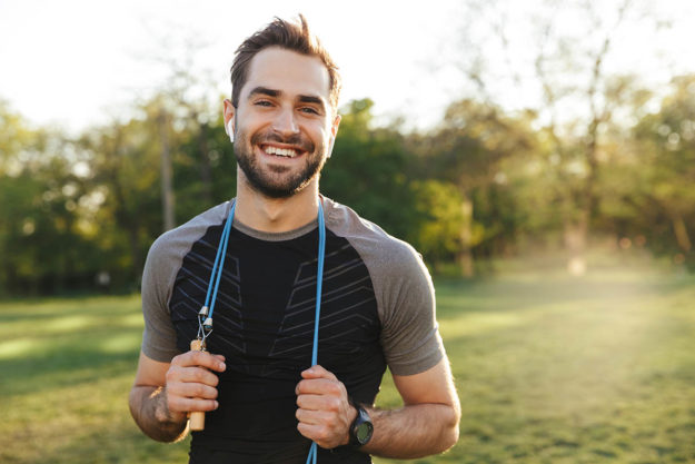 man in field smiling looking athletic giving Tips For Relapse Prevention