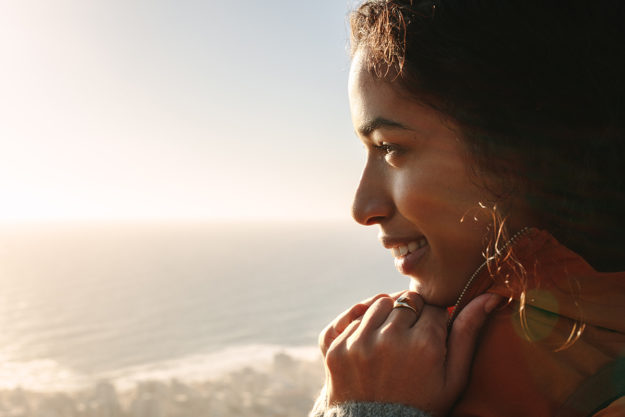 woman smiling looking out over ocean having a sober summer