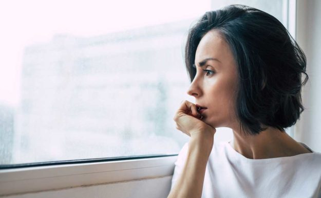 woman looking out window thinking about co-occurring disorders