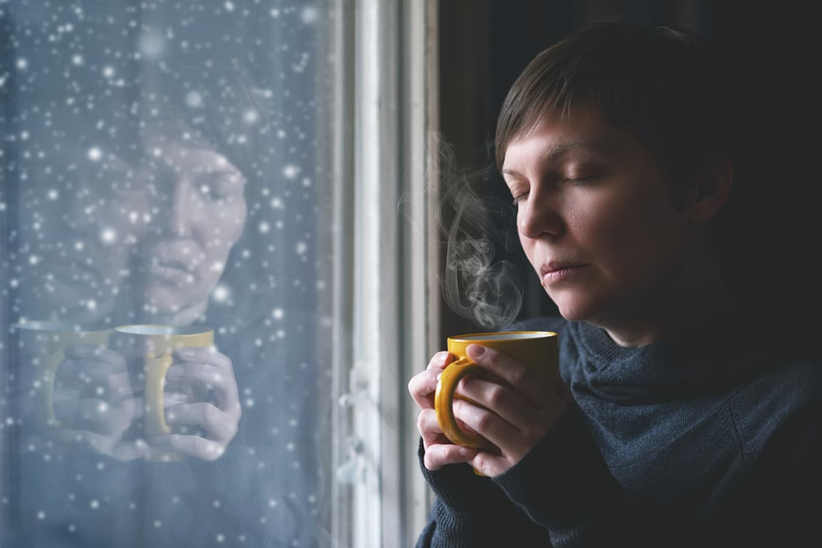 woman at window dealing with seasonal depression
